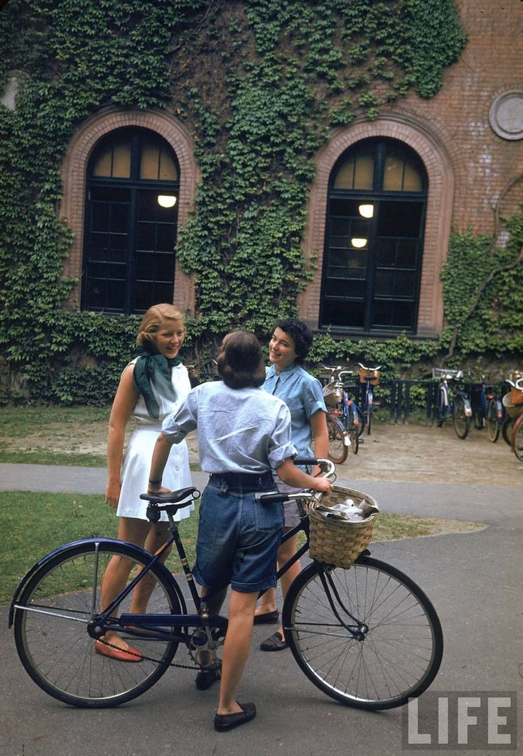 """""""A student with a bicycle talks with two classmates near an ivy-covered wall on the campus of Smith College, Northampton, Massachusetts, 1948."""" Photo by Peter Stackpole."""