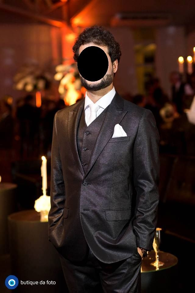 Noivo com terno preto brilhoso, colete do mesmo tecido, camisa branca e gravata branca perolada