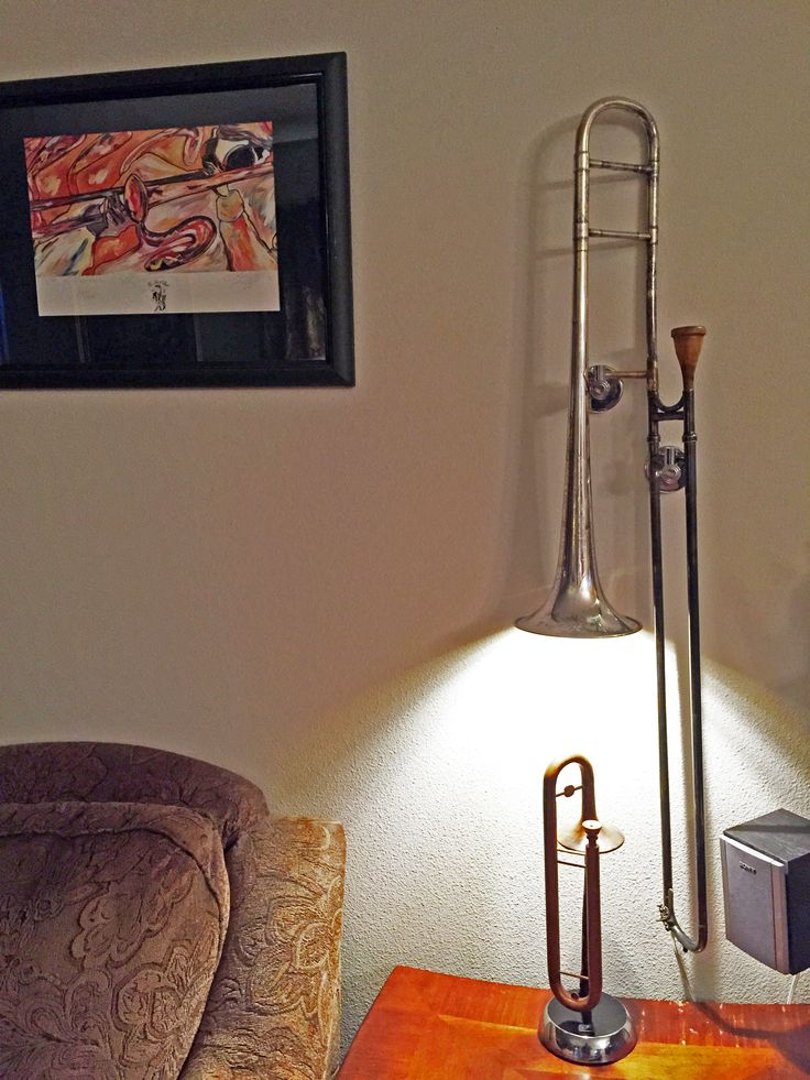 """The Otterstad Trombone Sconce created from a piece of trombone history. A 1905 H.N. White trombone """"The King"""" trombones of this era the slides were hand worked by Henderson N. White himself.  The switch is below the small wooden trombone.  Yes the mouthpiece on the silver trombone is wood."""