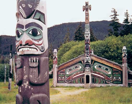 A Tlingit community house and totem poles are preserved in Totem Bight State Historical Park in Ketchikan, Alaska.