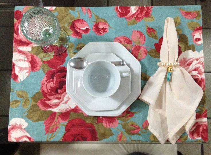 Jogo Americano em tecido Acquablock (ipermeável) estampa floral coral com fundo azul turquesa. <br> <br>Obs. <br>Valor de uma unidade do lugar americano. Guardanapos, porta guardanapos, sousplat não estão inclusos neste valor. <br> <br>Também temos à venda guardanapo de tecido, porta guardanapo e sousplat de crochê que compõem esta mesa.