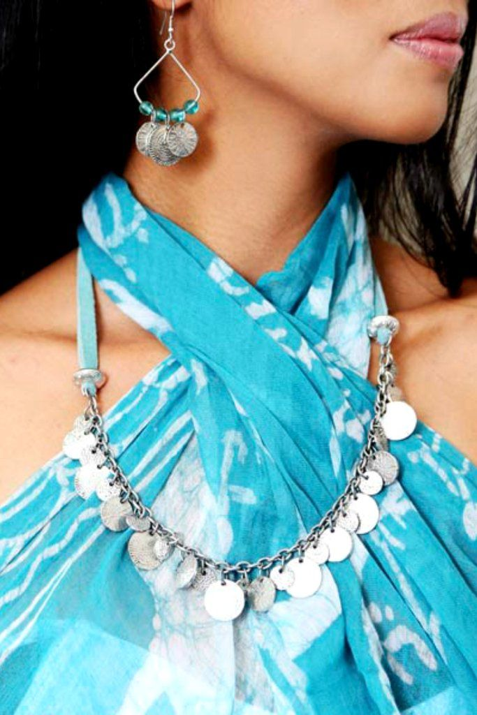 Fair Trade Coin Necklace  Our dazzling Fair Trade Coin Necklace exudes a traditional, yet modern and vibrant feel. Overlapping handmade silver toned metal coins gently dangle from a soft turquoise leather cord.   This Fair Trade Coin Necklace is completely handmade by Fair Trade Artisans in India where the art of Jewelry making is a proud cultural tradition. This Fair Trade necklace not only looks & feels good, it does good.