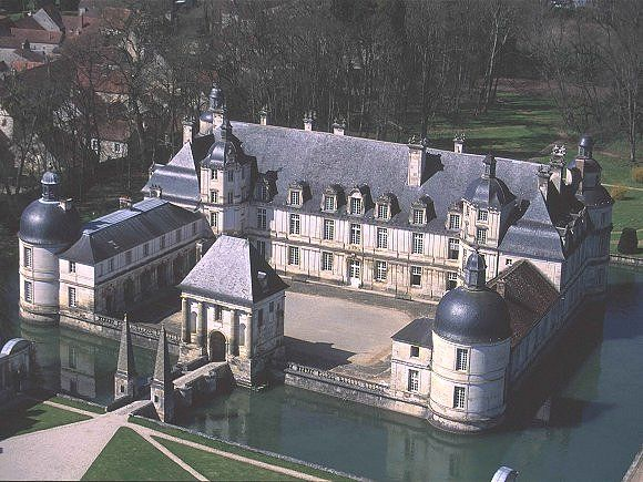"""Château de Tanlay- 10) CHATEAU DE TANLAY, ARCHITECTURE EXTERIEURE: Le """"Grand château"""" occupe les 3 côtés d'un quadrilatère entouré de douves. L'architecte initial pourrait en être Bertrand de Cazenove, de St Florentin. On accède à la cour par la porterie construite par Le Muet: en face s'élève le corps de logis principal, bâtiment d'un étage  flanqué de chaque côté par 2 courtes ailes que prolongent 2 bâtiments de moindre hauteur."""
