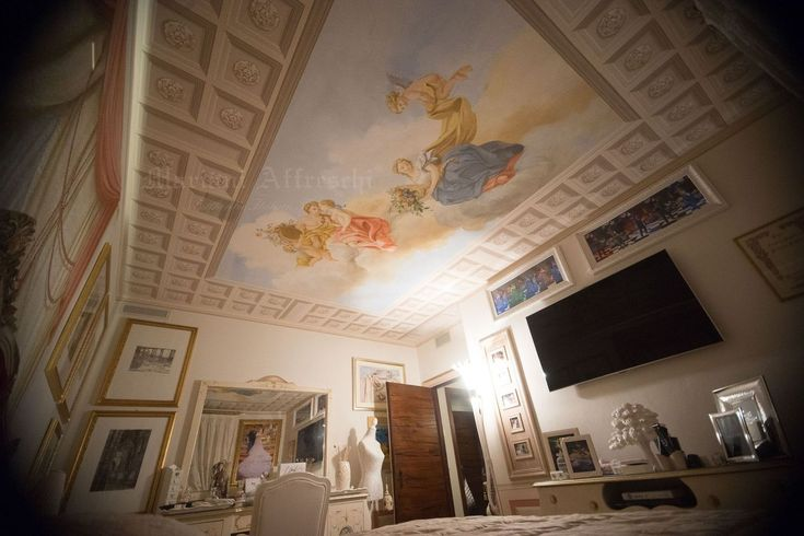 A ceiling painted to give a coffered effect with classic figures in the sky, painted by Mariani for a special bedroom