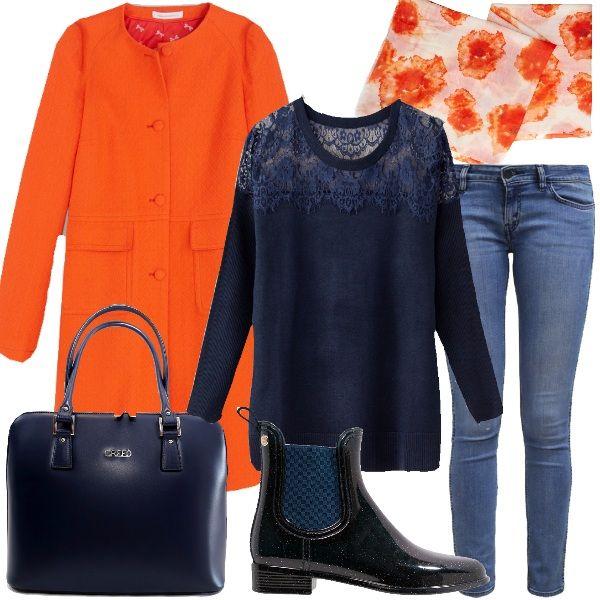 Outfit in cui, capi base come il jeans alla caviglia e il pullover blu, vengono resi unici dal cappotto arancio abbinato alla sciarpa di Benetton. Borsa da giorno e stivaletto in gomma blu a completare il look.