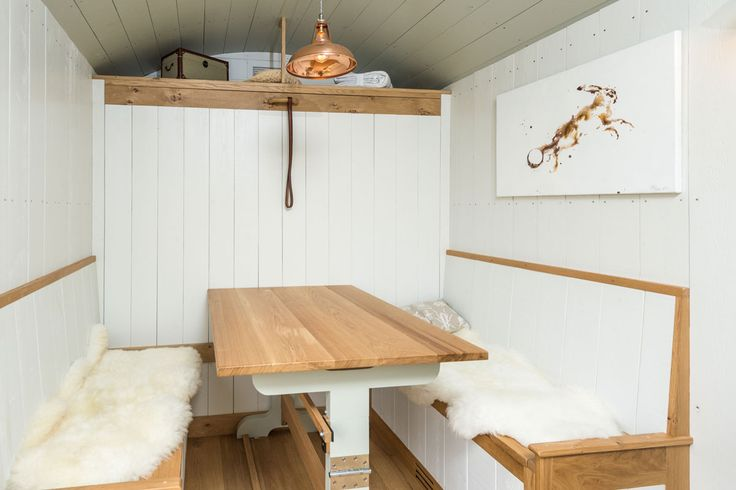 Tiny house with murphy bed above breakfast nook with pop-up table. Blackdown Shepherd Huts. UK.
