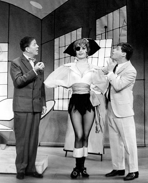 Publicity photo of Rudy Vallee, Virginia Martin and Robert Morse from the Broadway production of How to Succeed at Business Without Really Trying from 1961, public domain via Wikimedia Commons.