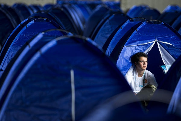 A young man from Spain sits in his tent between hundreds of other blue tents at the Campus Party Europe technology festival inside a hanger of former airport Tempelhof in Berlin, Germany.    Markus Schreiber/AP