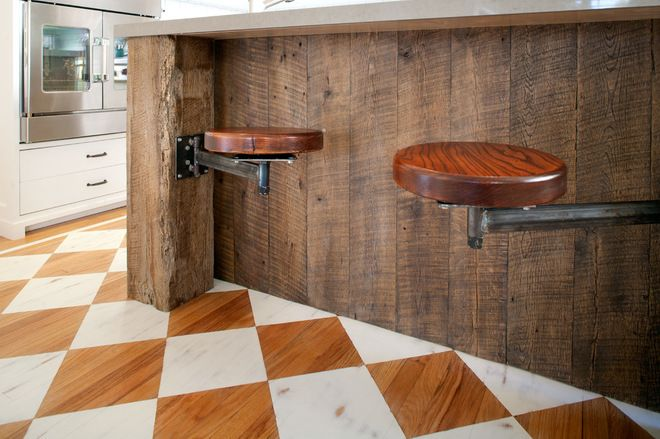 The island's large size meant there wasn't much space left between it and the custom built-in pantry wall. So Troyer designed custom swing-arm stools that wouldn't cramp the walking path. Brilliant !