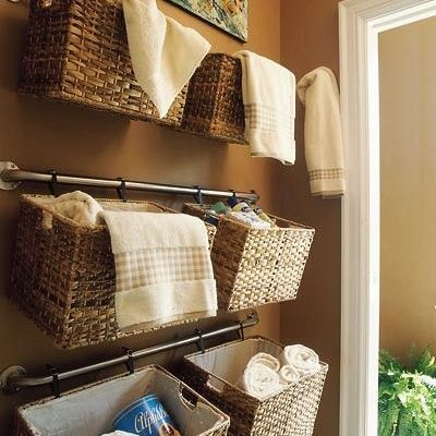 Hang baskets on towel bars to take advantage of unused wall space. The baskets can be attached with zip ties or  S hooks. This is a perfect idea for storing extra hand towels in the bathroom, organizing kids' toys, keeping craft items together, or even storing items in the garage.