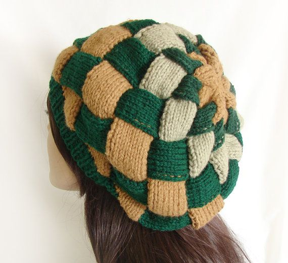 Womans knit winter hat. Knit in a woven-look beret style. A knitting technique called entrelac, was used to construct this gorgeous knit beret. Entrelac is an old technique meaning woven.  Colors: Dark green, tan and beige  Loose fitting and roomy hat; can be worn slouchy  Wear it pulled down or as a slouchy hat  Hand knit with 100% acrylic yarn  Measures (un-stretched): 11 inches diameter; 10.5 inches from center top to bottom edge; 22 inches circumference (stretched) of the lower narrow…