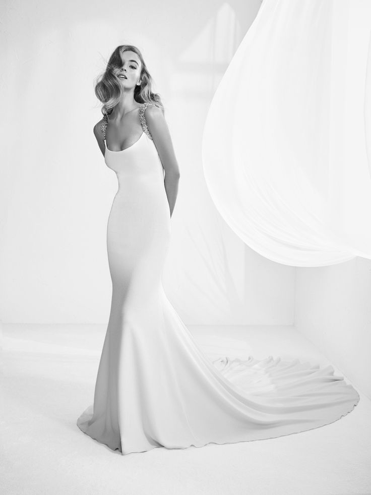 Rafia: Elegant mermaid style dress with round neckline and jewelled straps. Deep back and spectacular draping with train.