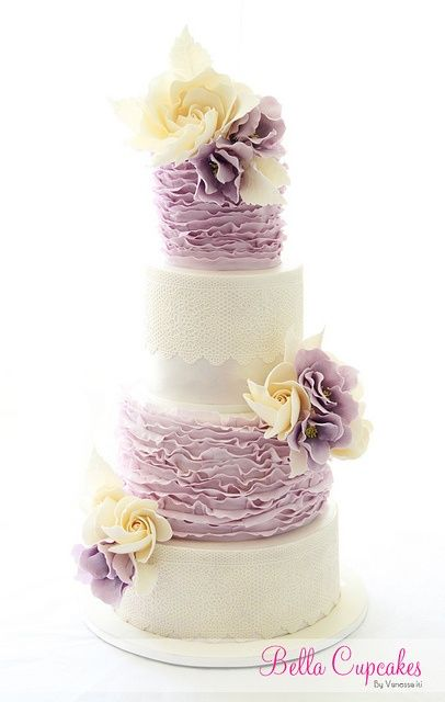 Beautiful layered wedding cake with ruffles and fondant flowers - love the color scheme of lilac and cream