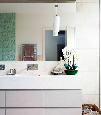 A neutral palette with splashes of green makes for a calm and functional family bathroom. Floor, wall tiles and mosaic tiles from Signorino Tile Gallery. Vanity casing in Laminex in Oyster Linea, top and basins from Apaiser. Tapware from Capitol Building.