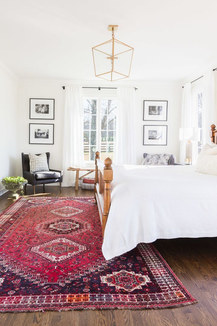 bedroom with white walls, white bedding, antique rug, seating