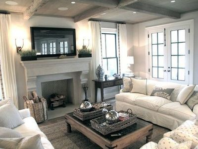 living rooms - rustic wood coffered ceiling French doors TV stone fireplace herringbone firebox white drapes ribbon trim sisal rug white slipcover sofas gray pillows chunky wood coffee table