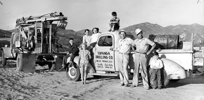 This is the work party to drill the well for the Community House in Topanga, California, 1952. On the fender is Dickey Alley, and on the hood, next to the windshield is Diane Molloy, Judy Alley is next to her on the hood. Also pictured are Meg, Ray and Doug Alley. Ray Alley and Frank Molloy owned Topanga Drilling Company. Topanga Historical Society. San Fernando Valley History Digital Library: Valley History, History Digital, Work Party, San Fernando, Fernando Valley, Community House, Digital Collections