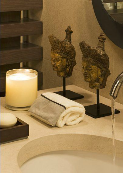 pair of small buddha statues rolled towels and candles