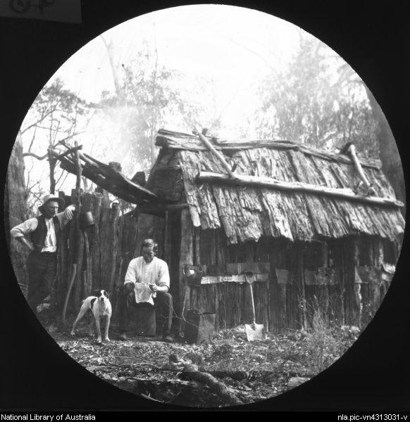 Two men, splitters, and a dog outside a slab hut, Australia, ca. 1900…