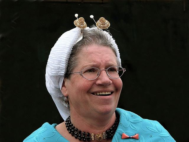 Dame in Scheveningse klederdracht   meerrijïg halssnoer van rode gitten of bloedkoralen. Verder sluit de vrouw haar zondagse doek met een gouden speld die het meest overeenkomt met de vorm van de boeken van haar hoofdijzer.  Roel Wijnants, via Flickr.