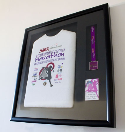 a framed t shirt and medal