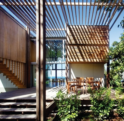 The pergola contains and frames the house and view from street and beach by Architecture Workshop