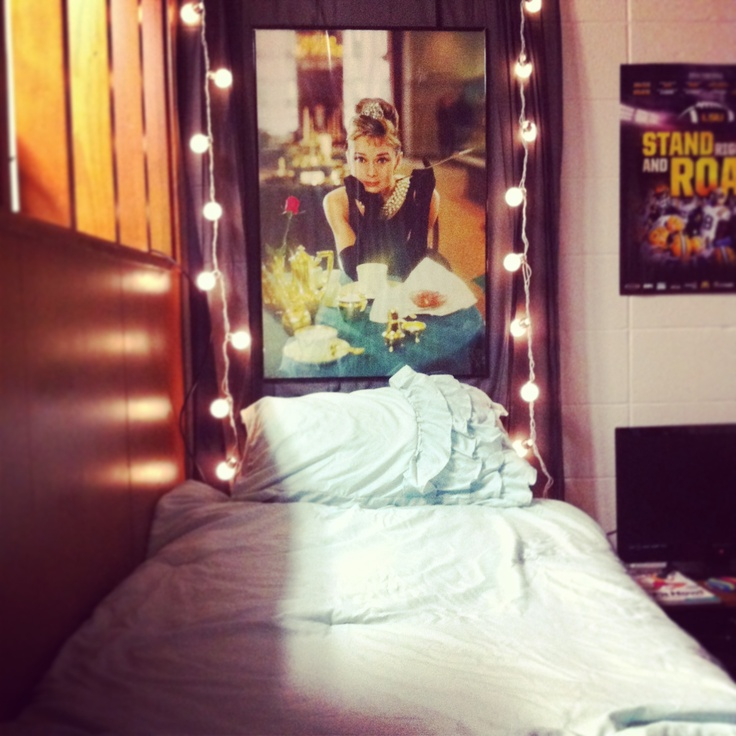 Dorm DIY curtain headboard with 2 string lights and a framed poster attached with command strips ...