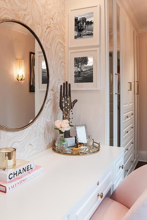 Glam dressing room boasts a blush pink upholstered chair placed before a white makeup vanity topped with a Regina Andrew Equestrian Tray and hand jewelry holder placed under a round gold mirror. #UpholsteredChair