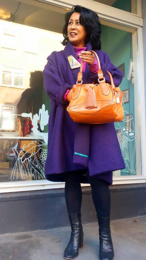 Bij Mode Met een Missie combineren wij de nieuwe collectie, met onze bijzondere secondhand items.  Het model draagt dit keer een secondhand tas en blouse van Vivienne Westwood. Daaroverheen draagt ze een nieuwe paarse capejas van gekookte wol. De broche van karton en papier is gemaakt door Jacqueline van Lent. De laarzen zijn van het model zelf.
