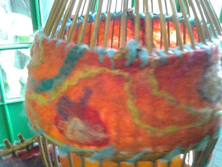 Detalle de lámpara jaula de mimbre intervenida en fieltro artesanal