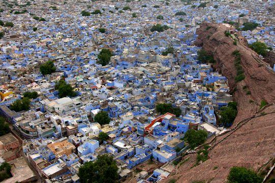 """Ancienne capitale du Mârvar et deuxième ville de l'État du Rajasthan en Inde, Jodhpur est surnommée """"la ville bleue"""", et cela se comprend très vite... pour la couleur des maisons de sa vieille ville aux ruelles labyrinthiques, qui prennent une dimension encore plus spectaculaire au soleil et depuis les remparts en hauteur"""