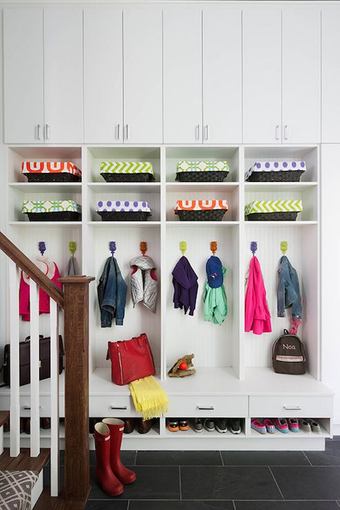 Family friendly mudroom features closed cabinets stacked over open cubbies filled with baskets and open lockers, one for each family member, above built-in bench with pullout drawers and shelves for shoes atop black slate tiled floor.