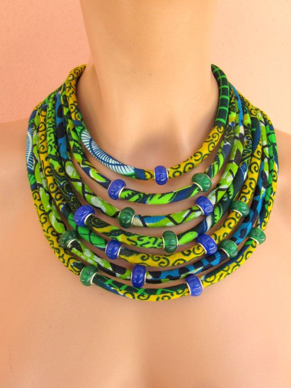 This is a Statement green necklace that is made of African wax fabric cords. The 7 cords are sewn and fitted around acrylic fiber. This awesome African inspired, trendy color necklace , worn on dressy or casual clothes will definitely be noticed. I have also added glass pearls just in the center of the necklace to give it a slight extra modern touch (Due to a shortage of the green beads I will add the same number of the total beads in blue only) that adds to its ethnic but chic look…