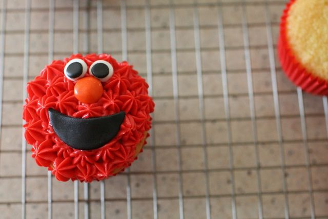 Let's start out with the easiest 0f the four characters – Elmo.  Fill a pastry bag fitted with a small star tip with red frosting.  (There are many, many tips that will work for this look.  Just use whatever you prefer.)  Cover the surface of the cupcakes in an even layer of red piped frosting. Eyes and mouth out of fondant; nose is an m