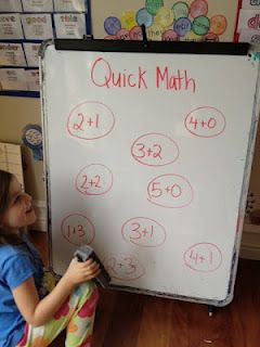 Quick Math: One student calls out an answer while the other erases the problem.