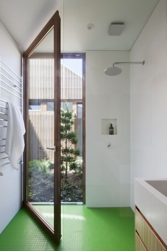 A large glass door opens out from the bathroom into a courtyard area