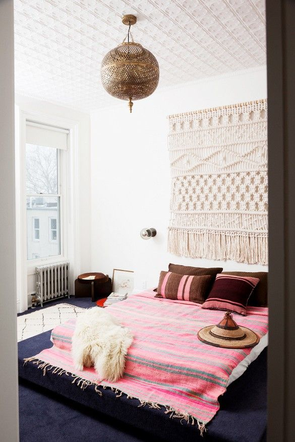 Bedroom with textured ceiling and gold Moroccan light fixture, pink bed, and tapestry on wall
