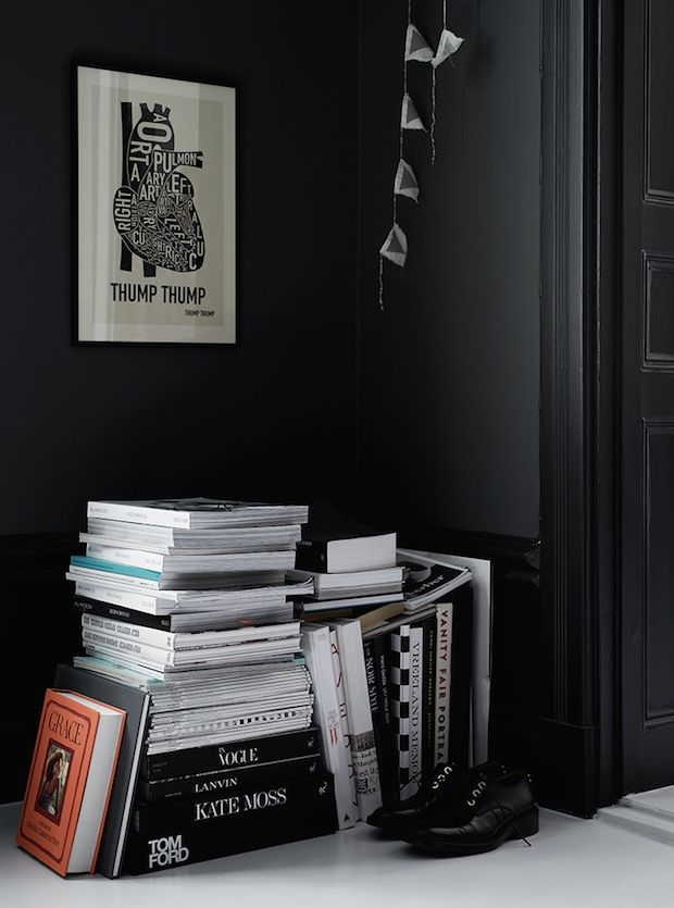 Books piled on the floor in a black and navy Swedish home. Kristofer Johnsson / Sasa Antic.