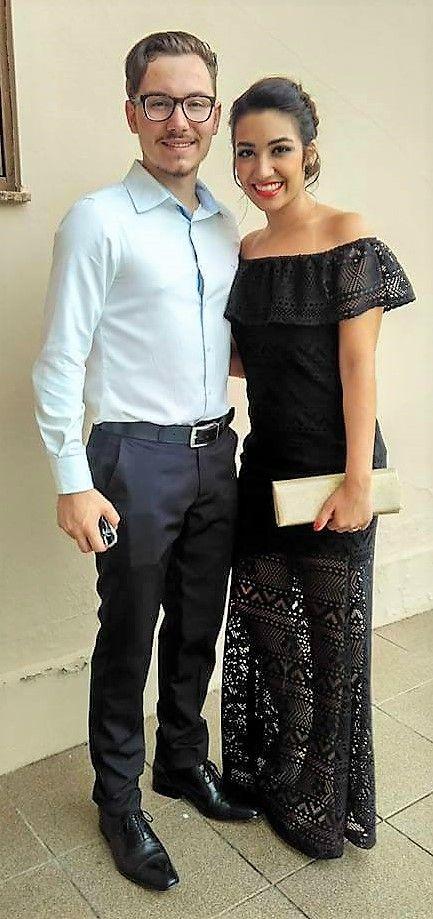 Look de casal para casamento. Vestido preto longo, sapato e bolsa dourada, batom vermelho, olhos pretos esfumados.