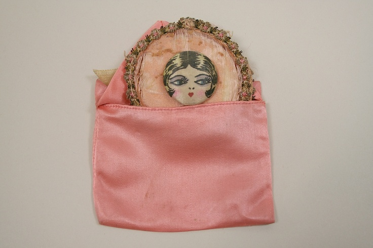 During the 1920s all the stylish woman would have a boudoir set to carry with them when out. The flapper face silk button would be used for the garter while the powder puff in silk envelope would be carried with them to use to powder their knees!