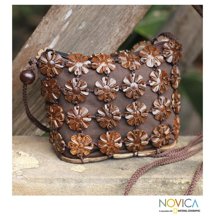 Compact and beautiful, this petite shoulder bag is crafted by hand. Sasithon Saisuk transforms coconut shells into flowers and links them with mango wood beads over brown cotton.