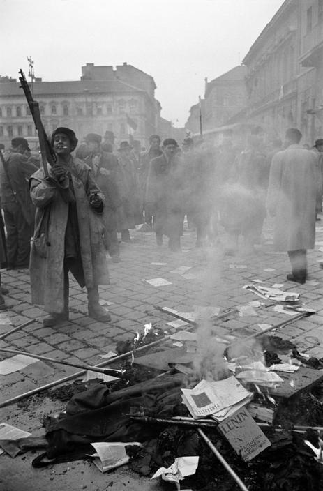 "In front of the offices of the Secret Police, members of the Hungarian insurrection destroy Soviet propaganda and portraits of Stalin. Budapest, 1956. Photo by Erich Lessing. ""The Hungarian Revolution of 1956 was a spontaneous nationwide revolt against the government of the People's Republic of Hungary and its Soviet-imposed policies. Despite the failure of the uprising, it was highly influential, and came to play a role in the downfall of the Soviet Union decades later."