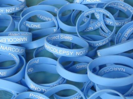 """Show your support! These light blue silicone bracelets read """"NARCOLEPSY: NOT ALONE""""  and """"Project Sleep"""" on the outside. SHIPPING INTERNATIONALLY. Packets of 5 bracelets are available in two sizes!"""