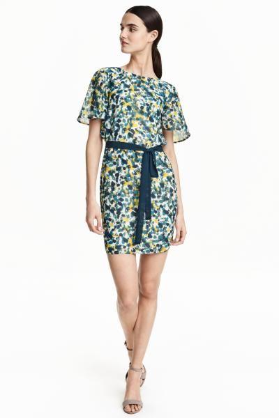 Шифоновое платье : Короткое прямое платье из шифона. На платье короткие рукава-крылышки и глубокий вырез сзади с широкими завязками на шее. Съемный пояс. На подкладке.