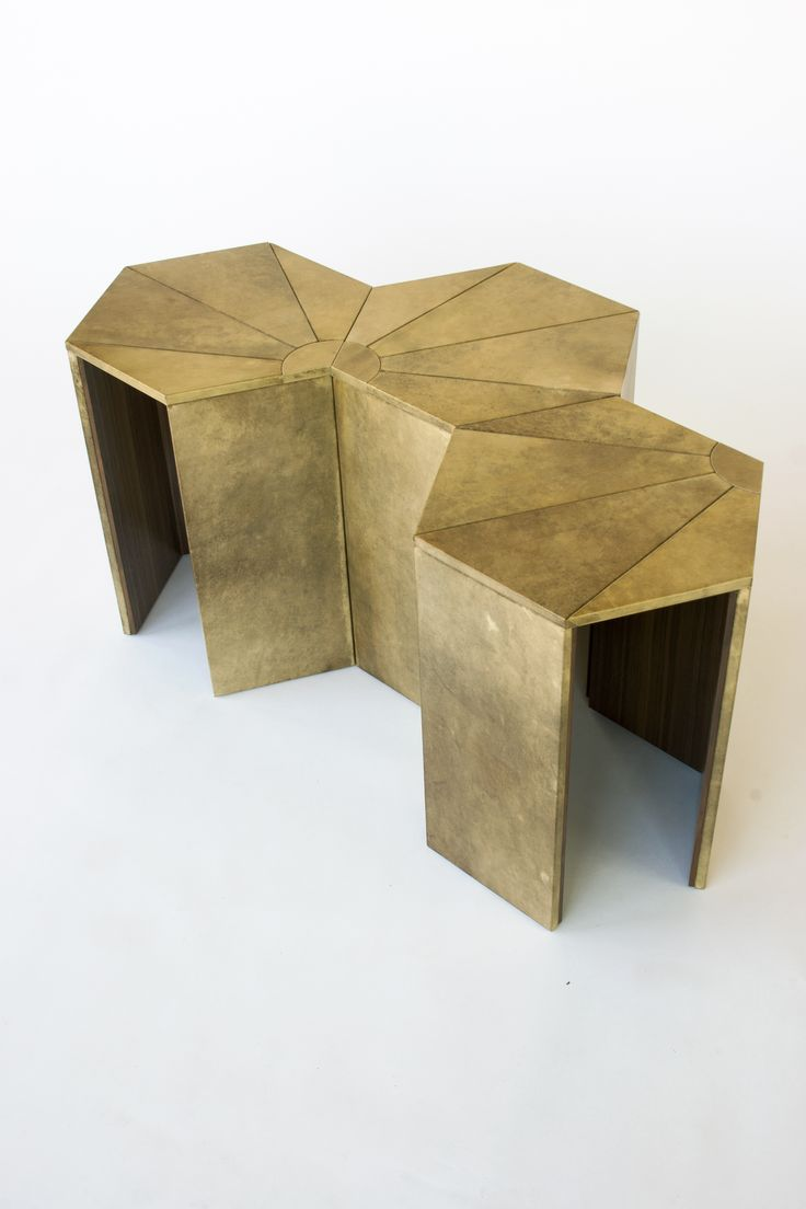 The Helios side table features a hexagon top and wide legs covered in parchment with a natural wood interior.  The top's geometric sun pattern combines with additional tables to create multiple shapes and patterns while providing a larger table surface.  Pictured in goat parchment and walnut.