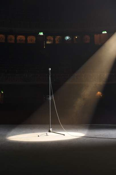 Microphone in spotlight on empty theater stage