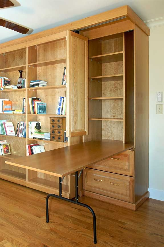 Murphy bed with side cabinet featuring built in fold out table for extra work space