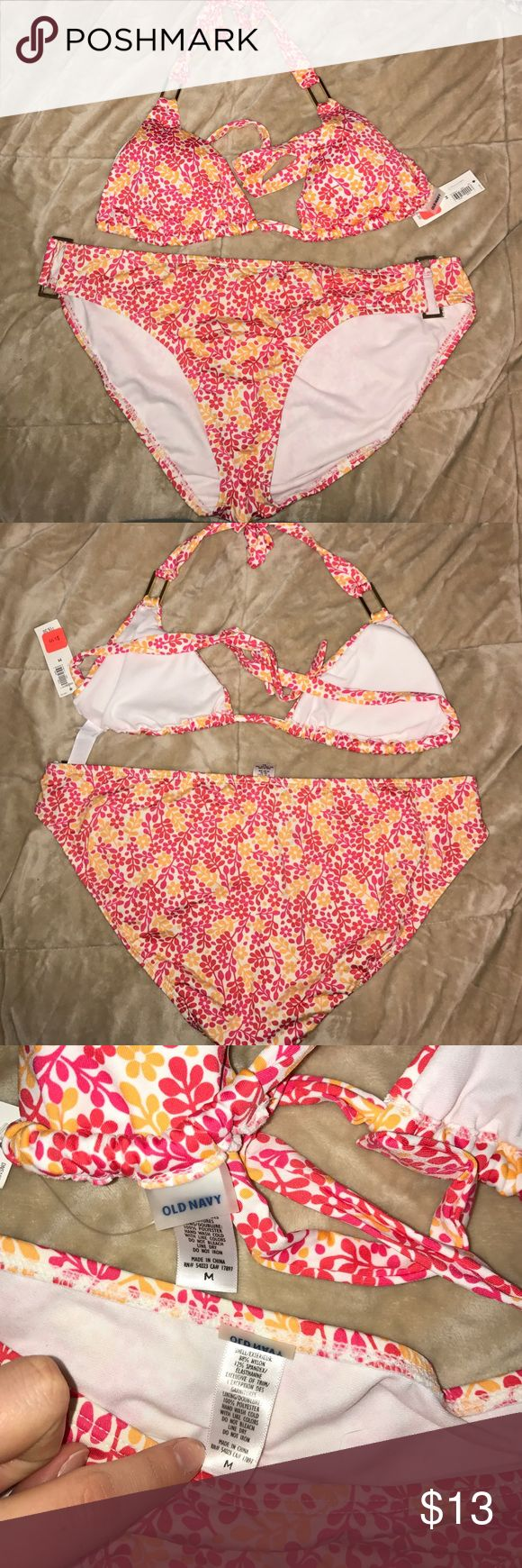 Old Navy orange and pink/red flower suit Bikini with a triangle top with gold rectangles. Has removable bra pads. The bottoms have the matching gold rectangles. It's a white suit with orange, pink, and red flowers. Old Navy Swim Bikinis