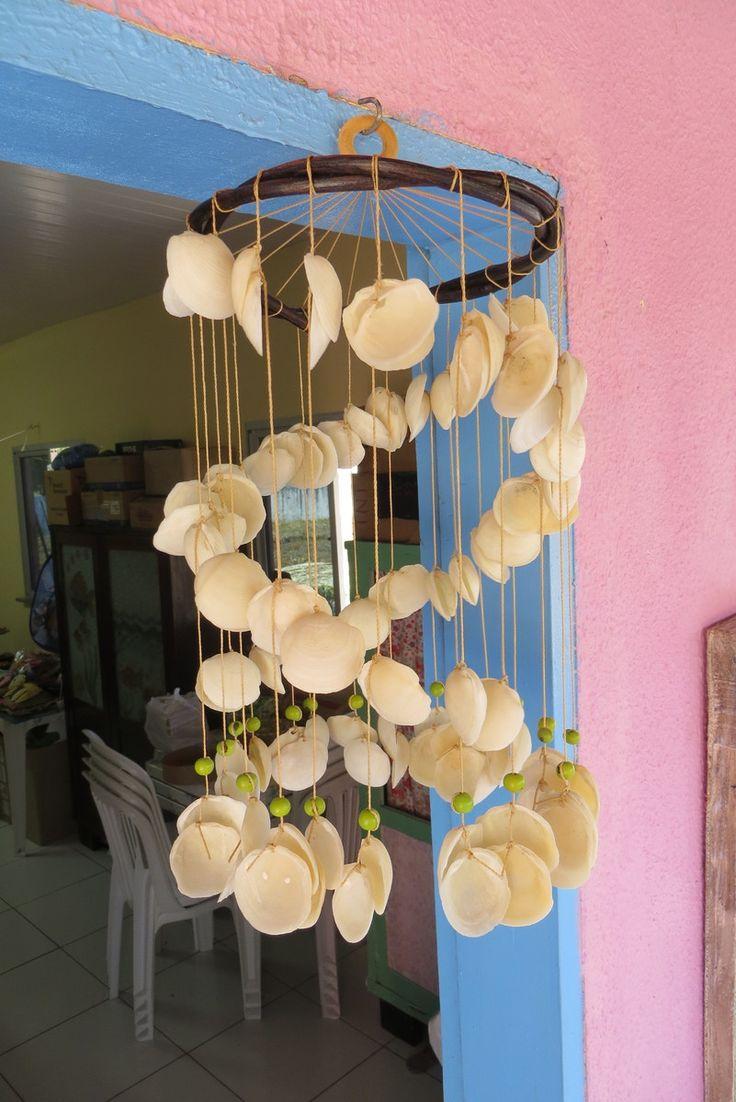 Confeccionado com conchas marinhas, fio encerado, cipó e caroços de açaí tingidos na cor verde. Ideal para a decoração de varandas e casas de praia. Cada modelo é único, podendo ser reproduzidos com o mesmo tipo de conchas, escamas e/ou cores de sementes, mas por trabalharmos com produtos naturai...