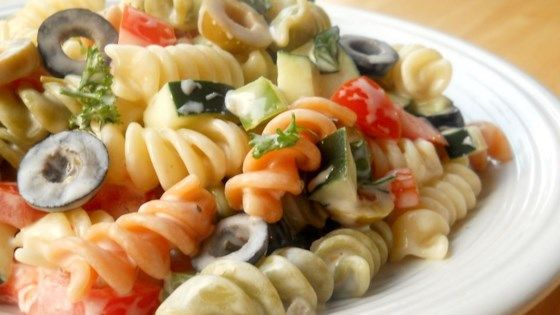Tomatoes and basil, fresh from the garden, are tossed with olives, bell peppers, rotini pasta, then dressed with a creamy, piquant blend of mayonnaise, red wine vinegar and garlic. Let the salad chill overnight to bring out the snappy flavors.